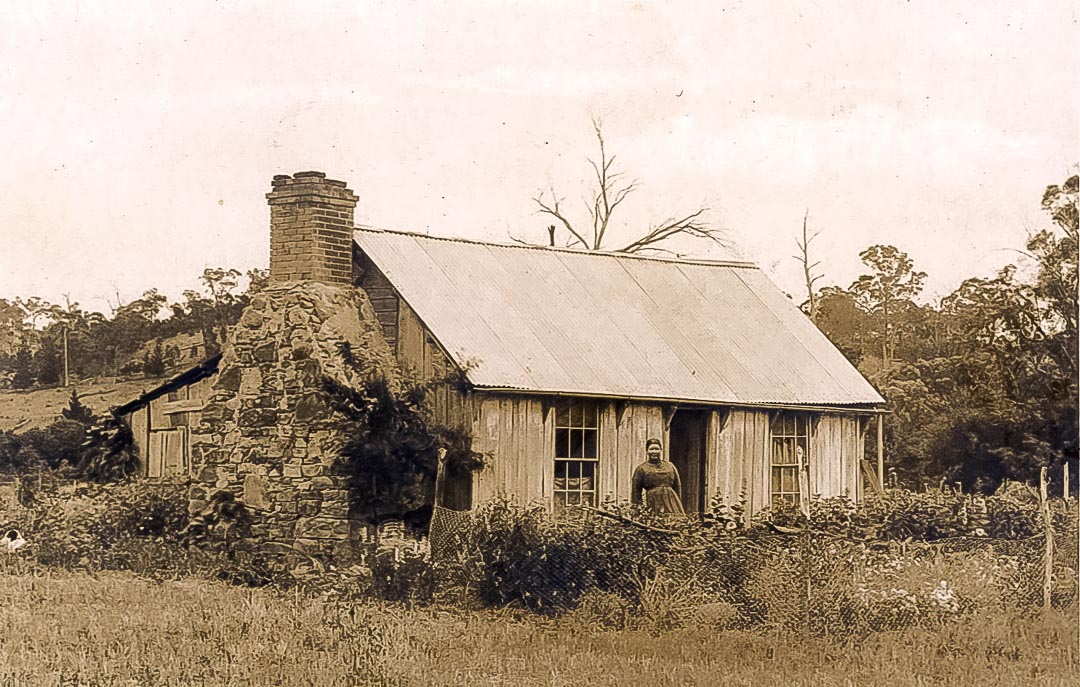 John Ryder's original dwelling was typical of many in the district and was constructed using slabs and palings from local river gum or stringy bark, and then lined with paper.  It was relocated to the Draper property 'Barton Hill', Yan Yean, and used as a kitchen and pantry.  Maria Pickard (1849 - 1925), eldest daughter of Charles and Catherine Draper in the foreground.  Photo credit James Chester Draper