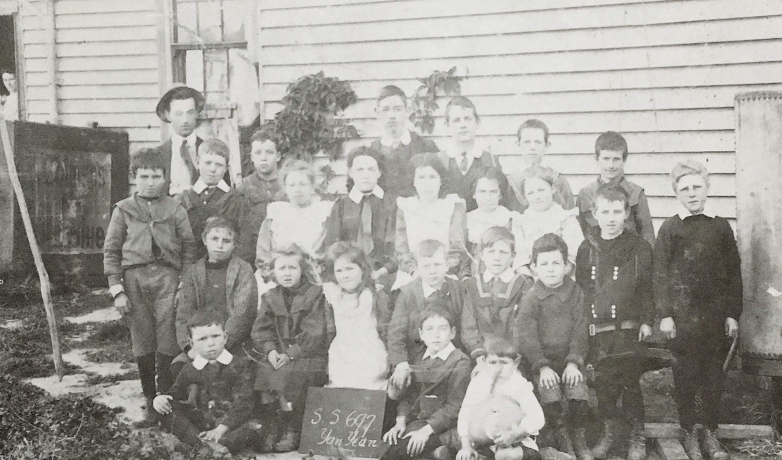 Yan Yean State School No. 697, c 1911.  Back Row: Mr Babbage, Glady Olney, George Wilson, Myles Merrilees, Don McKenzie. Third Row: Harold Boyes, Ken McPhee, Cathie Draper, Ida Wilson, Myrtle McIntosh, Lily Wilson, Hazel Hurrey, Jack McKenzie. Second Row: Jack Hancorne, Sally Hancorne, Doris Hurrey, Chester Draper, Tom Draper, Alec Mann, Walter McDonald. Front Row: Archie Andrews, Roy Smith, George McIntosh.  There were over thirty children attending the Yan Yean State School when we Draper siblings started school there. There were eight grades and one teacher – Alfred Babbage who was Teacher from 1909 to 1918. He was strict and used the strap fairly freely. He was also bad tempered but put his whole life into his job. All nine of us gained our Merit Certificate