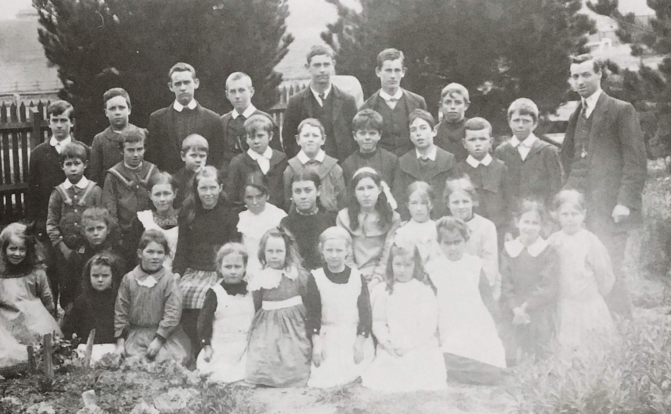 Yan Yean State School No. 697, c 1913.  Back Row: Don McKenzie, Ken McPhee, George Wilson, Myles Merrilees, Glady Olney, Eric McKenzie, Jack Hancorne. Third Row: George McIntosh, Jack McKenzie, Percy Bradford, Chester Draper, Harold Boyes, Roy Smith, Archie Andrews, Tom Draper, Mr Babbage. Second Row: Sally Hancorne, Phoebe Andrews, Cathie Draper, Jessie Olney, Lily Wilson, Sarah Boyes, Myrtle McIntosh, Eve McIntosh, Hazel Hurrey, Viola McLaughlin, Dora Merrilees. Front Row: Evelyn Welsh, Dorrie Hurrey, Muriel Draper, Grace Wilson, Lily Draper, Muriel Olney, Dorothy Boyes.  My father had started his school days at Hazel Glen private school in Chapel Lane, which is now part of the Doreen area. The School was run by Mr. and Mrs. Smith. My father and some other members of the family had each to take six pence to school on a Monday. If there was no money, they were sent home. A State School No. 1666 was opened at Arthurs Creek in 1876.  Yan Yean became a State School in 1873