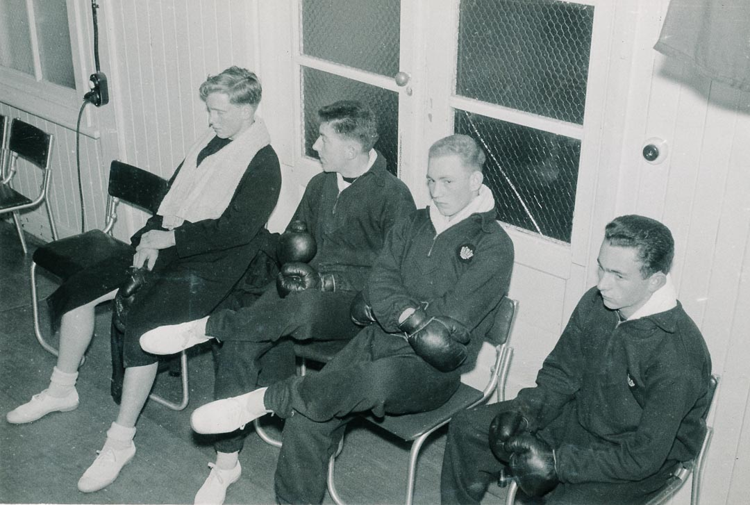 RANC, Boxing Finals, 16th July 1957.  Finalists waiting for their bout.  They were in the Green corner.  Left to Right: Bruce Draper, P. Bowler, R. Scott, R. Giles.  Awarded the Royal Australian Naval College  Shelley Cup for the best exhibition of the art of boxing in 1960, Bruce had a fearlessness that stood him in good stead all his life.  His boxing style was described as clean and aggressive
