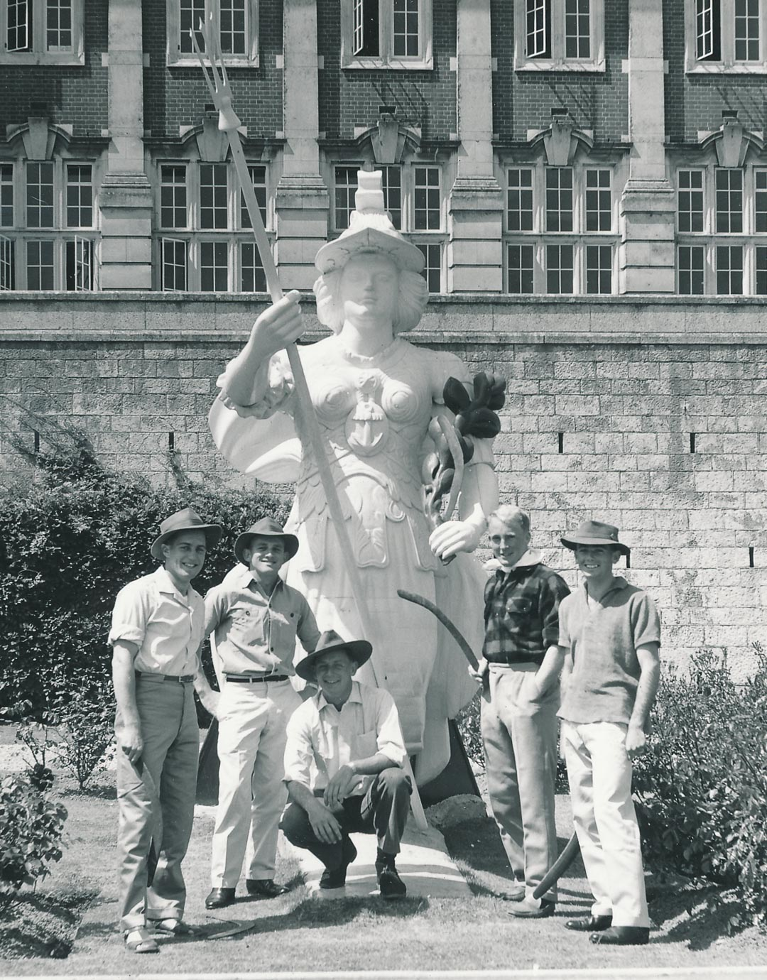 Left to right are John Davies, Tony Howland and Alex Bate.  Bruce is holding his boomerang in front of the figure of Britannia.  On the far right may be Don Chalmers.  Britannia Royal Naval College, Dartmouth, UK.  Information credit Ian Pfennigwerth